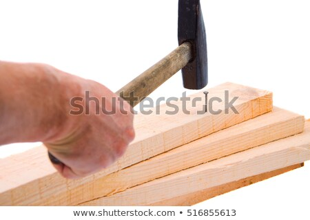 A hammer and a drived nail on a wooden board against a white background Stock photo © wavebreak_media