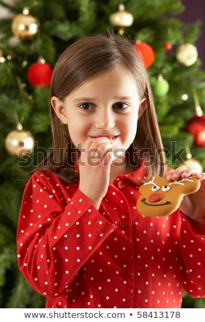 Young Girl Eating Reindeer Shaped Christmas Cookie In Front Of C Stock photo © monkey_business