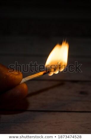 Burning matchstick held between the fingers Stock photo © erierika