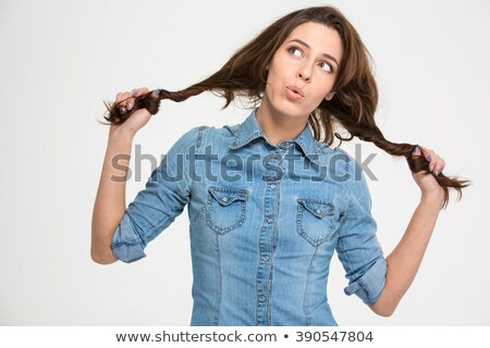 Playful woman grimacing and holding her hair as two braids  Stock photo © deandrobot