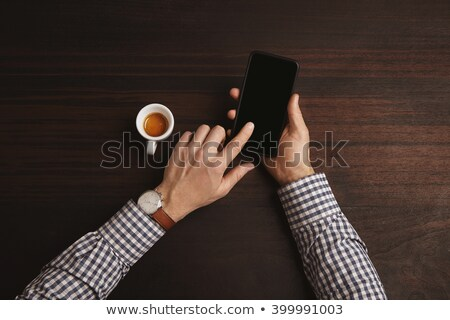 Man's Hands working with smartphone with financial report on screen Stock photo © Customdesigner
