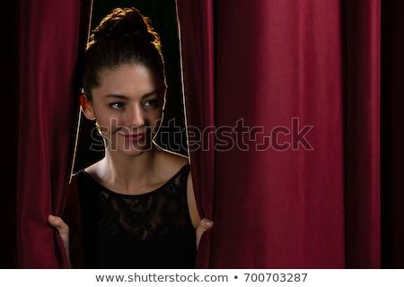Happy ballet dancer peeking through a stage curtain Stock photo © wavebreak_media