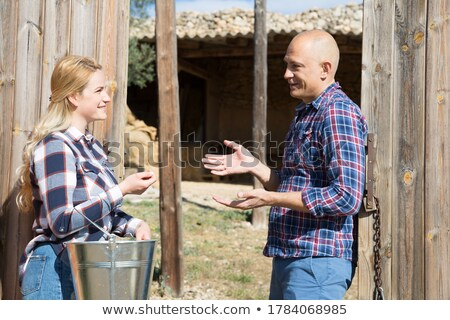 man and woman talking on country gate stock photo © is2
