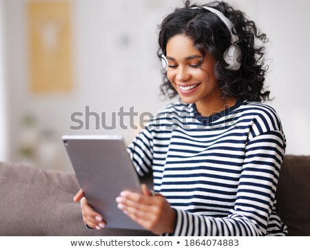 A young woman listening music on digital tablet  sitting Stock photo © 2Design