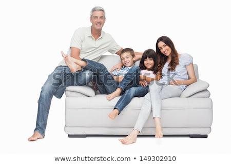 Family sitting on sofa smiling at camera on white background Stock photo © wavebreak_media
