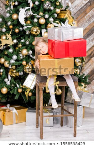 Little girl holding a box with a lot of Christmas silver and gol Stock photo © dashapetrenko