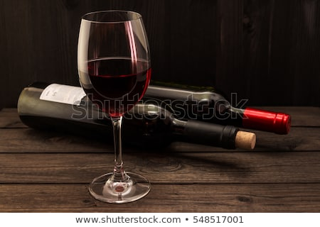 elegant glass of red wine with dark and red grapes on wooden board on black background space for te stock photo © denismart