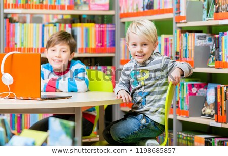 Brothers in the library reading books and listening to audio Stock photo © Kzenon