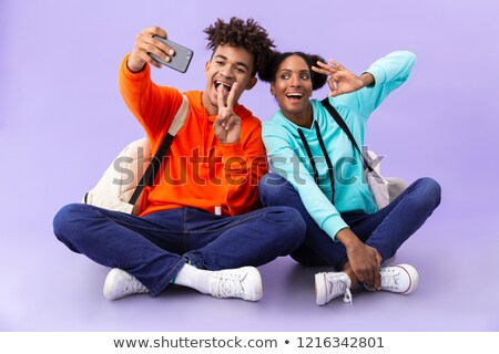 african american guy and girl wearing backpacks taking selfie ph stock photo © deandrobot