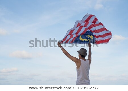 Young man travels in Malaysia. Holds the Malaysian flag Stock photo © galitskaya