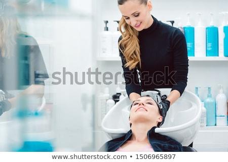 Artisan hairdresser washing hair of customer woman Stock photo © Kzenon
