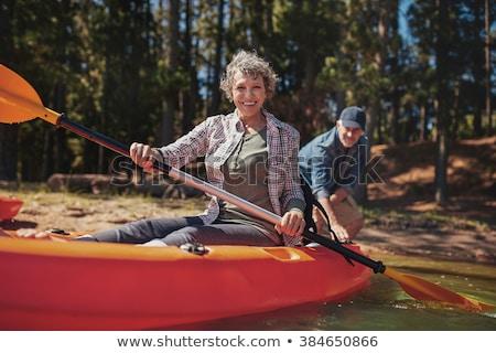 Happy couple kayaking on lake Stock photo © Kzenon