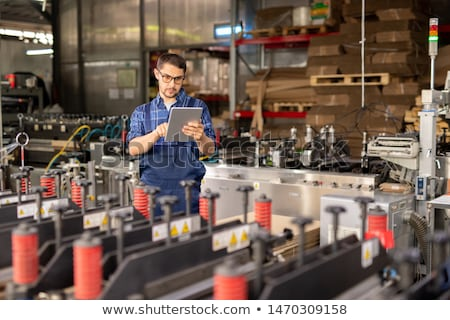 contemporary engineer of industrial plant using touchpad by workplace stock photo © pressmaster