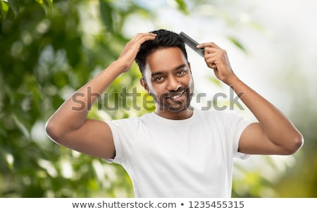 happy indian man brushing hair with comb Stock photo © dolgachov