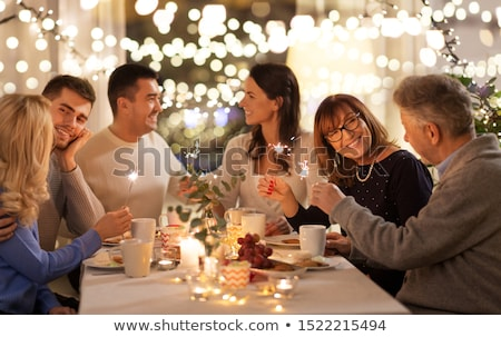 family with sparklers having dinner party at home Stock photo © dolgachov