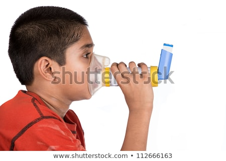 Close up image of a cute little boy using inhaler for asthma.  Stock photo © Lopolo