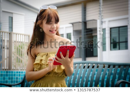Stylish woman using smartphone at poolside Stock photo © dash