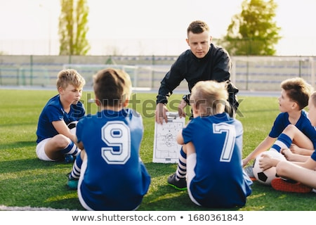 Young Soccer Trainer Coach Explaining Tactic on Team Sports Tactics Board. Children During Soccer Fo Stock photo © matimix