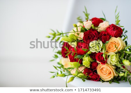 A woman in an elegant red dress and a bouquet of flowers in her hands stands with her back to the ca Stock photo © ElenaBatkova