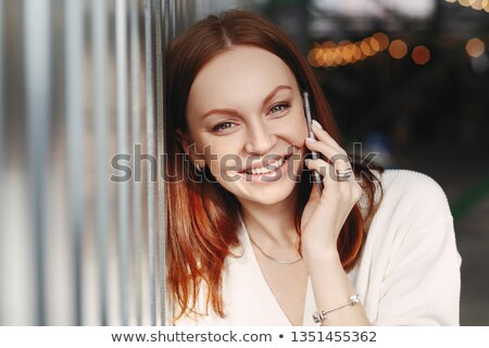Close up shot of cheerful woman with brown hair, has friendly mobile conversation, has make up, toot Stock photo © vkstudio