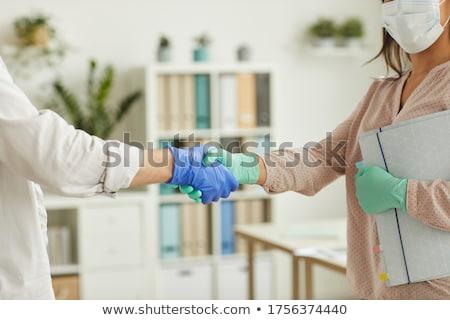 Duas pessoas aperto de mãos cirúrgico luvas Foto stock © nito