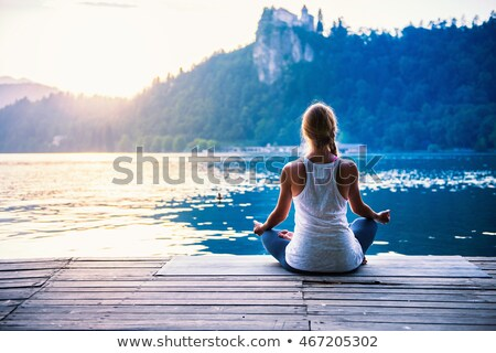 Wellness yoga woman practicing meditation in nature by watefall and lush forest. Banner panorama of  Stock photo © Maridav