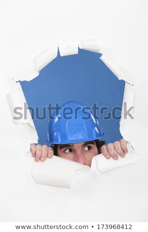 Tradesman peeking out through an opening in a wall Stock photo © photography33