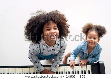 smiling girl playing her piano stock photo © sumners