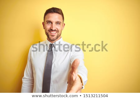 portrait of a smiling young business man offering a welcoming ha stock photo © hasloo