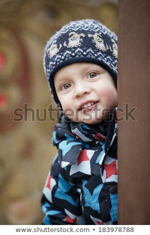 Cute little boy peering around a door Stock photo © d13