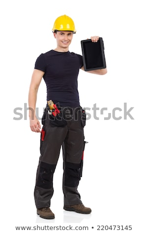 full length portrait of a smiling man showing tablet computer screen on gray background stock photo © deandrobot