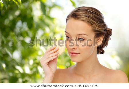 Stock photo: young woman cleaning face with exfoliating sponge