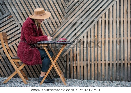 Laughing young woman sitting near fence outdoors Stock photo © dash