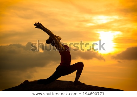 Woman in worrior yoga pose meditating at sunset. Zen Stock photo © photocreo