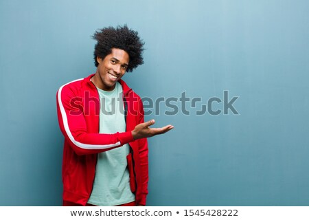 happy young african sportsman posing and pointing stock photo © deandrobot