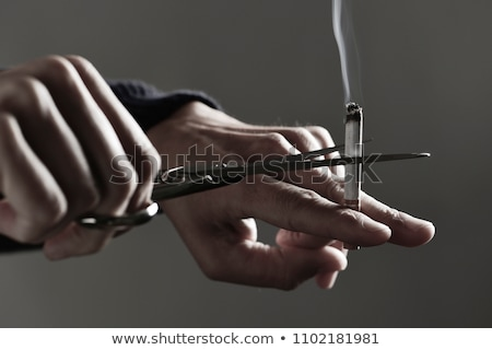 man cutting a lit cigarette with scissors Stock photo © nito