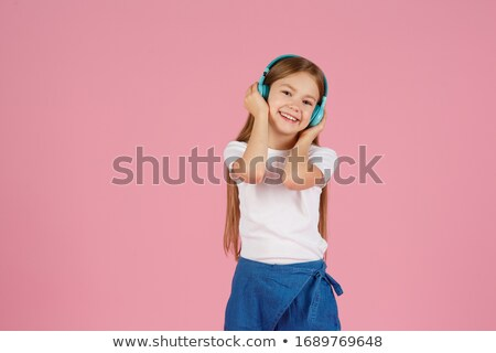Portrait of a smiling little schoolgirl listening to music Stock photo © deandrobot