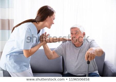 Caretaker Assisting Senior Man To Get Up From Sofa Stock photo © AndreyPopov
