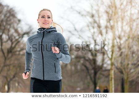 woman running down a path on winter day in park stock photo © kzenon