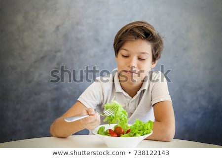 Teen boy refuses to eat salad Stock photo © boggy