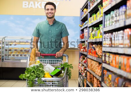 Man shopping in supermarket pushing his trolley with vegetables Stock photo © Kzenon