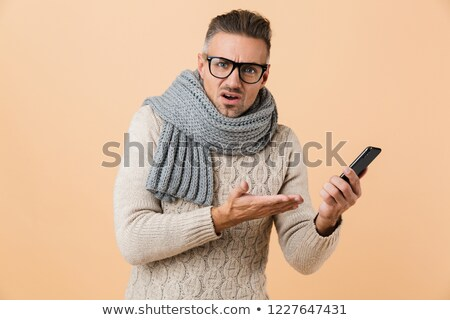 portrait if a puzzled man dressed in sweater and scarf stock photo © deandrobot
