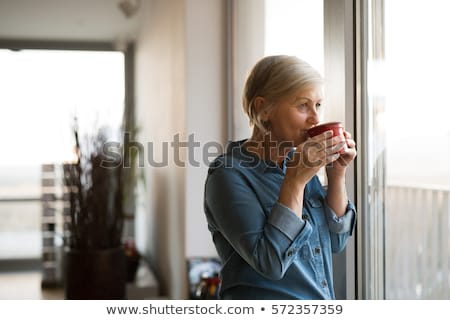 senior woman drinking tea at home stock photo © dolgachov