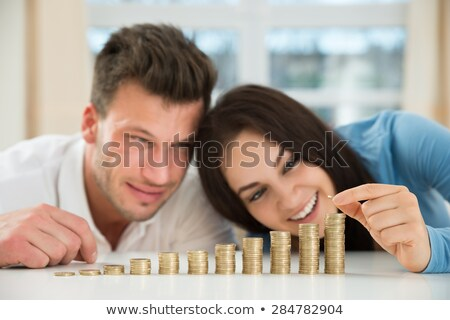 happy couple stacking coins stock photo © andreypopov