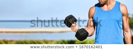 Bicep curl - weight training fitness man outside working out arms lifting dumbbells doing biceps cur Stock photo © galitskaya