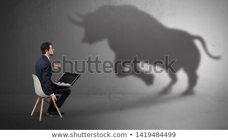 Businessman staying and offering stuffs to a huge bull shadow Stock photo © ra2studio