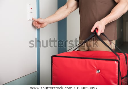 Pizza Man Ringing The Door Bell With A Large Bag Stock photo © AndreyPopov