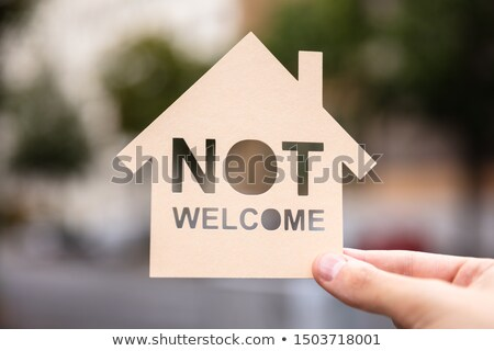 Hands Holding Paper With Cutout House And Non Welcome Words Stock photo © AndreyPopov