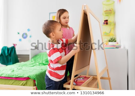 happy kids drawing on easel or flip board at home Stock photo © dolgachov