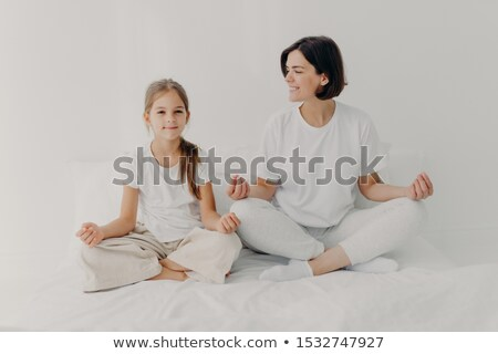 Horizontal shot of happy relaxed brunette mother and daughter pose in lotus pose, try to relax, keep Stock photo © vkstudio